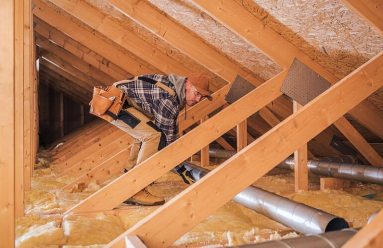 Heat Supply Insulation in New Houses. male-contractor-installs-metal-pipe-system-in-attic